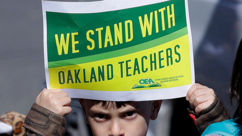 FILE - In this Feb. 21, 2019 file photo, a student holds up a sign while marching with parents, teachers and supporters outside of Manzanita Community School in Oakland, Calif. Striking teachers in Oakland are expected to vote Sunday, March 3, 2019 on a contract deal aimed at ending a seven-day walkout. The Oakland Education Association postponed the vote by a day after announcing earlier it would happen Saturday. The 3,000 teachers walked off the job Feb. 21, effectively shutting the city's 86 schools to demand higher pay, smaller classes and more school resources. (AP Photo/Jeff Chiu, File)