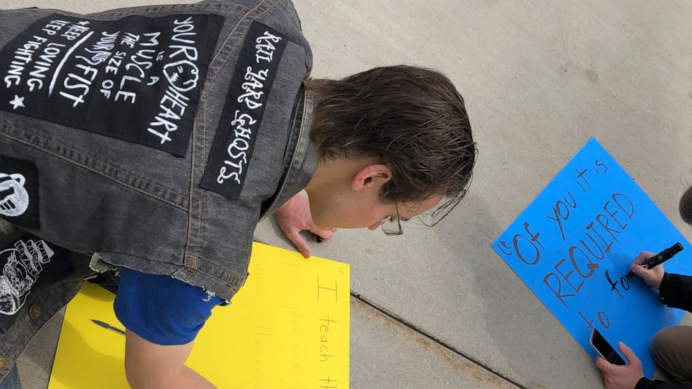 In this April 12, 2019 photo, Alex Laurenco holds a sign at a protest during a demonstration at Brigham Young University in Provo, Utah, about changes BYU students would like to see in how the Honor Code is enforced. A strict set of rules at Mormon-owned Brigham Young University banning things commonplace at many campuses such as drinking, premarital sex, beards and piercings is under new scrutiny — this time from students who want their university to be more compassionate with the punishments for violators. (Rick Egan/The Salt Lake Tribune via AP)