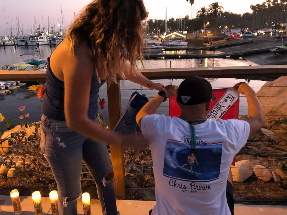 JJ Lambert, 38, and his fiancee, Jenna Marsala, 33, hang up a dive flag in remembrance of the victims of the Conception boat fire at a memorial site on Monday, Sept. 2, 2019, in Santa Barbara, Calif. A fire raged through the boat carrying recreationa