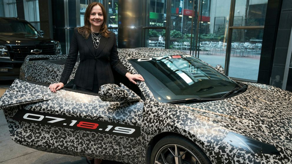 """This image provided by General Motors shows GM chairman and CEO Mary Barra standing by a camouflaged next generation Chevrolet Corvette Thursday, April 11, 2019 in New York. A new rendition of the classic sports car is coming. General Motors has a big change in store for the eighth generation Corvette being revealed July 18, 2019. The engine in the new model is being moved from under the hood, to be tucked between the passenger compartment and the rear wheels — a """"mid-engine"""" design. (Todd Plitt/GM via AP)"""