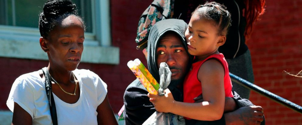 In this Monday, June 10, 2019 photo, Devation Powell, the father of slain 3-year-old Kennedi Powell, hugs his cousin Shylar Roberts, 5, as he sits near where Kennedi was shot the night before along Michigan Avenue in the Mount Pleasant neighborhood o