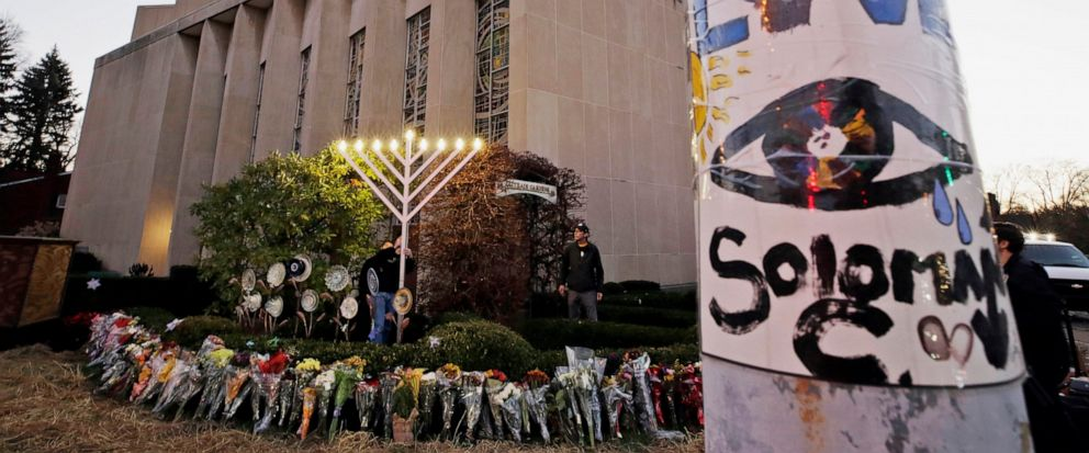 FILE - This Dec. 2, 2018, file photo shows a menorah at a memorial outside the Tree of Life Synagogue, where Robert Bowers killed worshippers in an Oct. 27 shooting, as people prepare for a celebration service at sundown on the first night of Hanukka