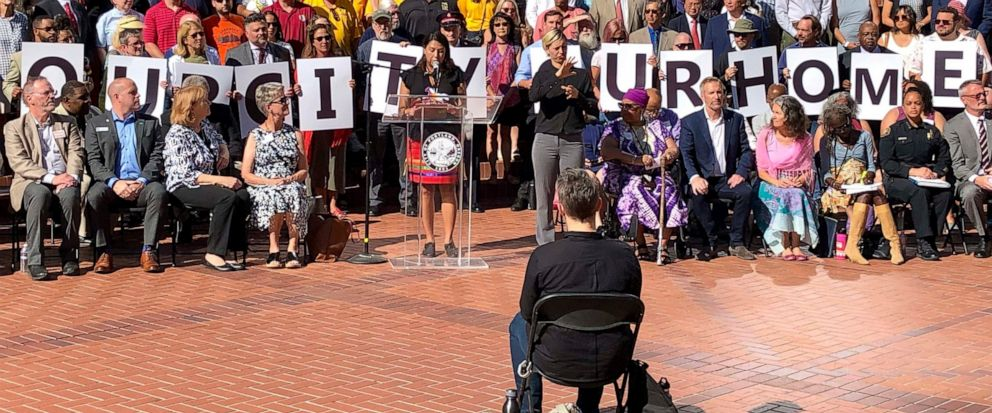 Members of dozens of civic leaders hold up signs spelling out Our City Our Home on Wednesday, Aug. 14, 2019, in Portland, Ore., during a rally to support the city in advance of protests planned for Saturday. The Mayor of Portland, Ted Wheeler, said a