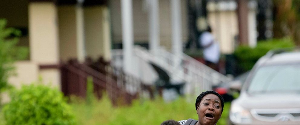 Terrian Jones reacts as she feels something moving in the water at her feet as she carries Drew and Chance Furlough to their mother on Belfast Street near Eagle Street in New Orleans after flooding from a storm dumped lots of rain on Wednesday, July
