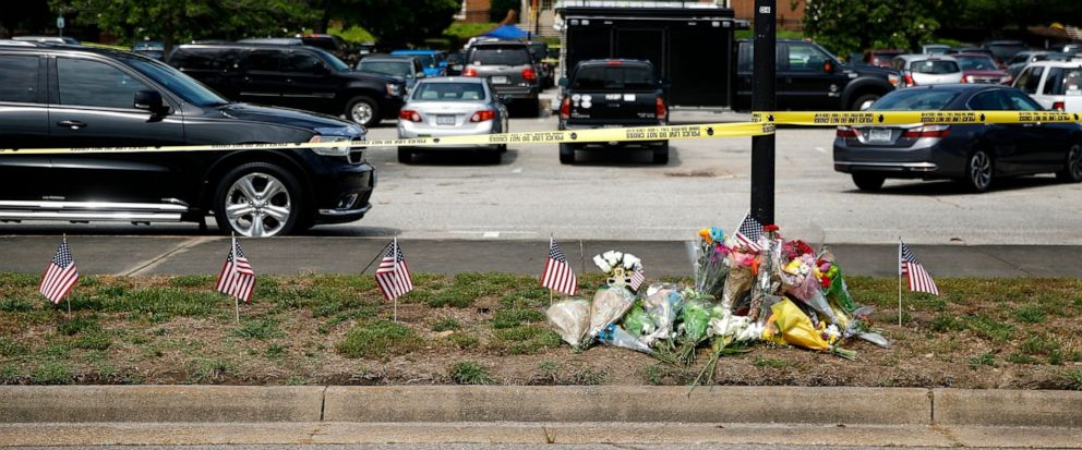 FILE - In this June 1, 2019 file photo, a makeshift memorial rests at the edge of a police cordon in front of a municipal building that was the scene of a shooting in Virginia Beach, Va. Four Virginia Beach Shooting victims' families say they think t