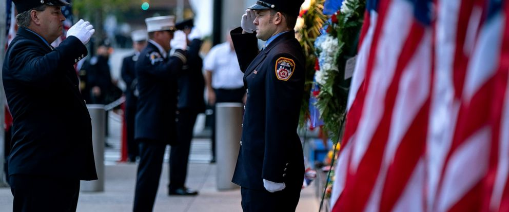 New York City firefighters salute in front of a memorial on the side of a firehouse adjacent to One World Trade Center and the 9/11 Memorial site during ceremonies on the 18th anniversary of 9/11 terrorist attacks in New York on Wednesday, Sept. 11,