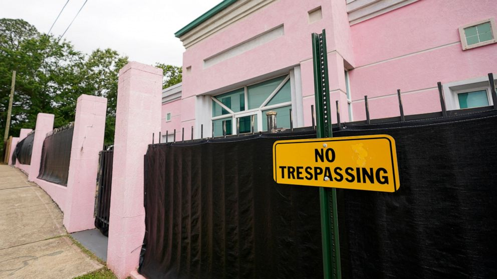 """FILE - In this May 19, 2021, file photo, the Jackson Women's Health Organization clinic, more commonly known as """"The Pink House,"""" is shrouded with a black tarp so that its clients may enter in privacy in Jackson, Miss. The Mississippi attorney genera"""