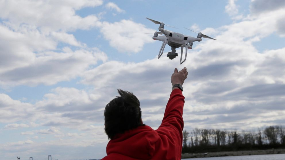 FILE - In this April 29, 2018, file photo, a drone operator helps to retrieve a drone after photographing over Hart Island in New York. Drone sightings reported by airline pilots over New Jersey renew questions about how to accommodate the popular devices into the nation's airspace. The ability of drones to interfere with aviation is likely to get worse as the number of machines multiplies. Many store-bought drones come with technology to prevent owners from flying them near airports, but there are hacks, and home-built machines don't necessarily include those protections. (AP Photo/Seth Wenig, File)