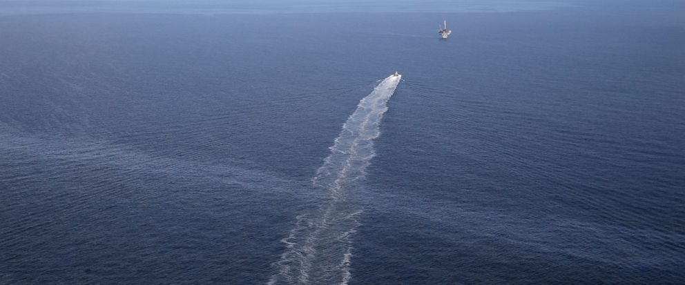 FILE - In this March 31, 2015 file photo, the wake of a supply vessel heading towards a working platform crosses over an oil sheen drifting from the site of the former Taylor Energy oil rig in the Gulf of Mexico, off the coast of Louisiana. The Coast
