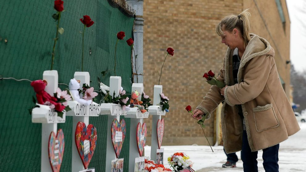 A woman places flowers at a makeshift memorial Sunday, Feb. 17, 2019, in Aurora, Ill., near Henry Pratt Co. manufacturing company where several were killed on Friday. Authorities say an initial background check five years ago failed to flag an out-of-state felony conviction that would have prevented a man from buying the gun he used in the mass shooting in Aurora. (AP Photo/Nam Y. Huh)