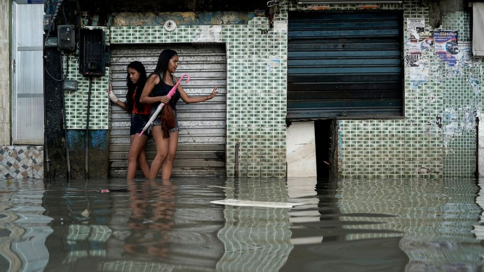 Women wade through a flooded street in Rio de Janeiro, Brazil, Wednesday, April 10, 2019. Heavy rains killed at least 10 people and left a trail of destruction in Rio de Janeiro on Tuesday, raising questions about the city's preparedness to deal with recurring extreme weather. (AP Photo/Leo Correa)