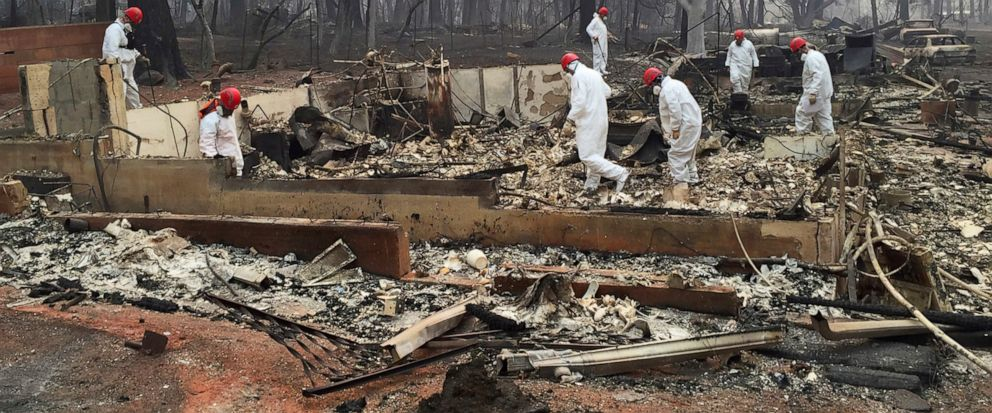 FILE - In this Nov. 15, 2018 file photo, volunteer rescue workers search for human remains in the rubble of homes burned in the Camp Fire in Paradise, Calif. California fire authorities say that Pacific Gas and Electric equipment was responsible for