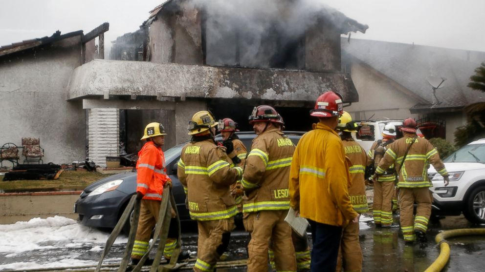 FILE - In this Sunday, Feb. 3, 2019 file photo, firefighters suppress a fire at the scene of a deadly plane crash in the residential neighborhood of Yorba Linda, Calif. A preliminary federal report released Thursday, Feb. 21, 2019, says the pilot whose plane broke up and crashed into a Southern California home was warned before takeoff that he was heading into bad weather. (AP Photo/Alex Gallardo, File)