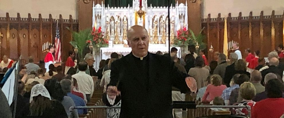 In this June 9, 2019 photo, Father Eduard Perrone conducts a choir during mass at Assumption of the Blessed Virgin March Parish in Detroit. The Roman Catholic Archdiocese of Detroit said Sunday, July 7 that it has removed Perrone from public ministry