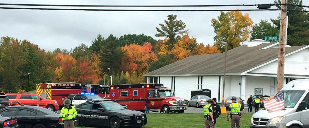 RETRANSMITTED WITH NEW SLUG AND BETTER QUALITY - In this photo provided by WMUR-TV, police stand outside the New England Pentecostal Church after reports of a shooting on Saturday, Oct. 12, 2019, in Pelham, N.H. WMUR-TV reports that Hillsborough Coun