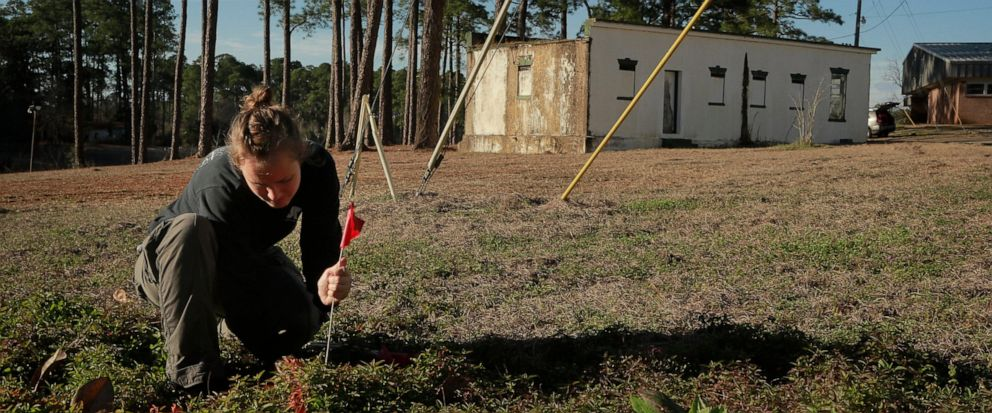 FILE- In this Feb. 4, 2014 file photo, University of South Florida anthropology student Meredith Tise marks a parcel of land to be examined with ground penetrating radar at the Arthur G. Dozier School for Boys, in Marianna, Fla. University of South F