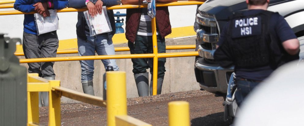 Handcuffed workers await transportation to a processing center following a raid by U.S. immigration officials at Koch Foods Inc., plant in Morton, Miss. U.S. immigration officials raided several Mississippi food processing plants on Wednesday and sig