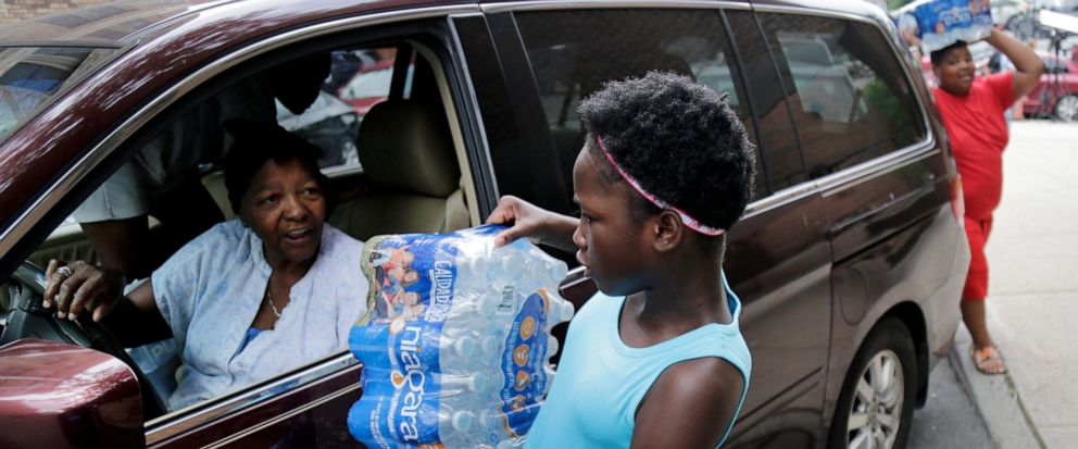 Elaine Younger, 11, and Tahvion Williams, 14, right, load water in their familys van at the Newark Health Department in Newark, N.J., Wednesday, Aug. 14, 2019. Residents began picking up bottled water on Monday, days after elevated lead levels were