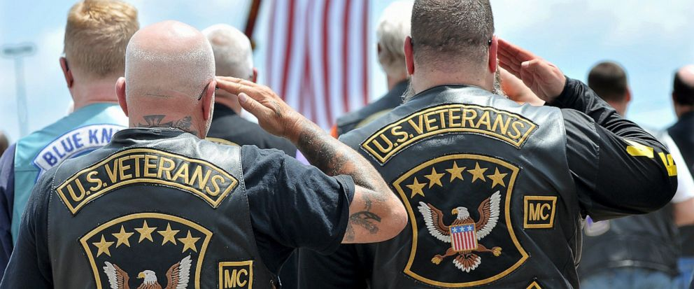 Members of the U.S. Veterans Motorcycle Club salute the flag during the playing of the National Anthem at the beginning of a memorial and remembrance service for seven motorcyclists and their spouses who died in the June crash Saturday, July 13, 2019
