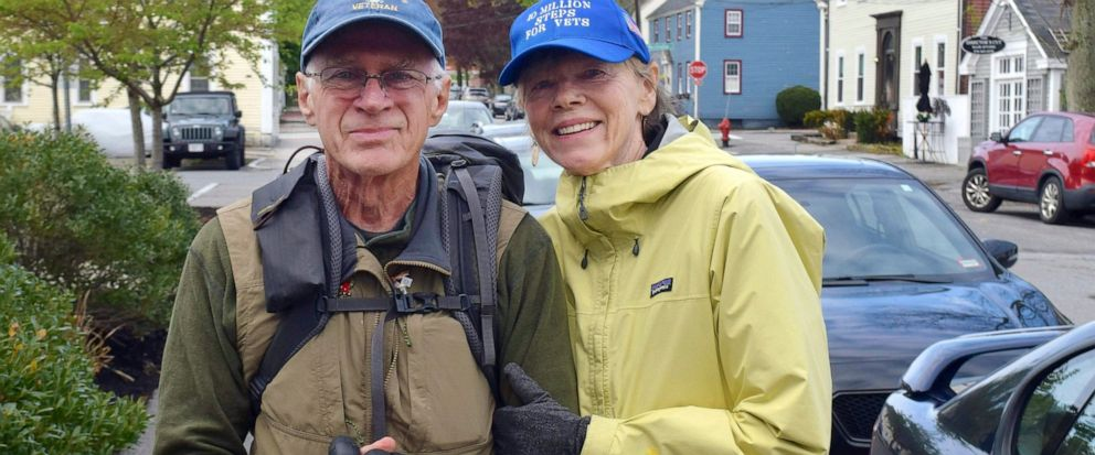 In this Wednesday, May 15, 2019 photo, U.S. Air Force veteran William Shuttlesworth, left, poses with his wife Patty on Market Street, in Newburyport, Mass., at the start of his planned cross-country hike to raise awareness for veterans issues. Shut