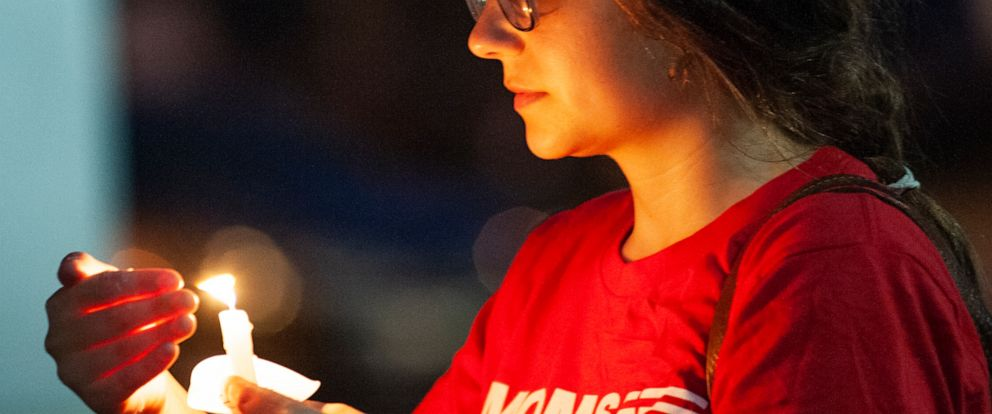 Hannah Gliemann shields her candle from the wind during an Interfaith Vigil for El Paso, Texas and Dayton, Ohio mass shooting victims hosted by the Jonesboro local group of the Arkansas Chapter of Moms Demand Action, Thursday, Aug. 8, 2019, at the Cr
