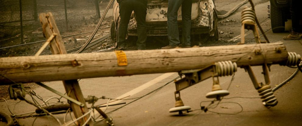 FILE - In this Nov. 10, 2018 file photo, with a downed power utility pole in the foreground, Eric England, right, searches through a friends vehicle after the wildfire burned through Paradise, Calif. Pacific Gas & Electric has agreed to pay $11 bill