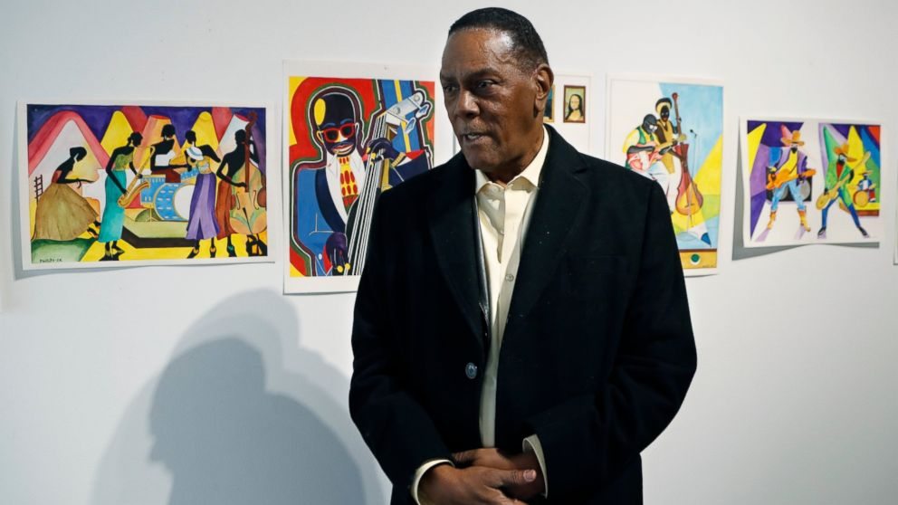 In this Thursday, Jan. 17, 2019 photo, Richard Phillips stands next to some of his artwork during an interview at the Community Art Gallery in Ferndale, Mich. Phillips was exonerated of murder in 2018 after 45 years in prison. Lawyers say he should be entitled to more than $2 million under Michigan's wrongful conviction law, but the state so far is resisting. So Phillips, 73, is selling some of his 400-plus watercolors that he painted in prison. (AP Photo/Carlos Osorio)