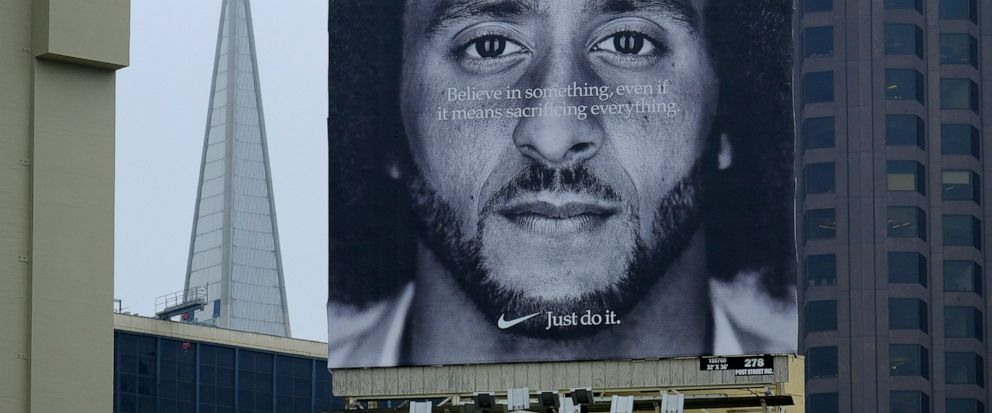 FILE - In this Sept. 5, 2018, file photo, a large billboard stands on top of a Nike store showing former San Francisco 49ers quarterback Colin Kaepernick, at Union Square in San Francisco. Nike is pulling a flag-themed tennis shoe after Kaepernick co