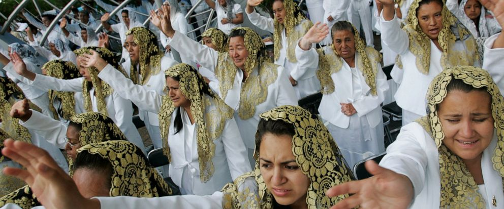"""FILE - In this Aug. 14, 2009 file photo, worshippers raise their hands at La Luz Del Mundo, """"Light of the World, Restoration of the Primitive Christian Church,"""" during the Holy Dinner celebration, one of the principal religious events of The Light of"""