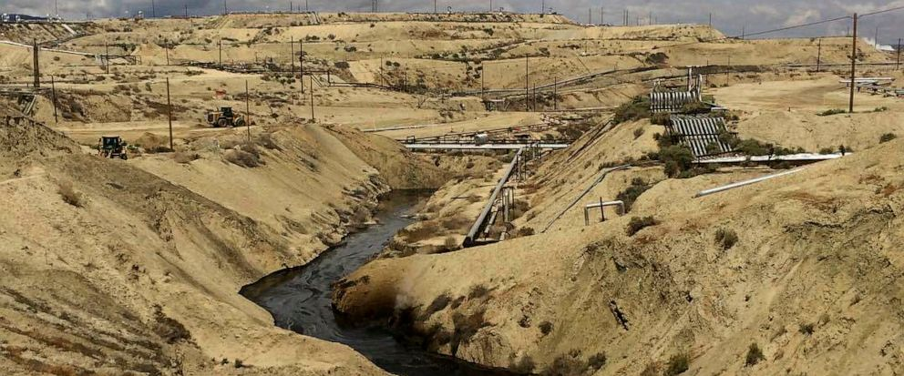 In this May 10, 2019 photo provided by the California Department of Fish and Wildlifes Office of Spill Prevention and Response, oil flows at a Chevron oil field in Kern County, Calif. Nearly 800,000 gallons of oil and water has seeped from the groun