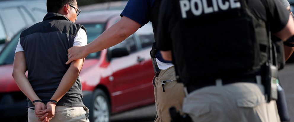FILE - In this Aug. 7, 2019, file photo, a man is taken into custody at a Koch Foods Inc. plant in Morton, Miss. Unauthorized workers are jailed or deported, while the managers and business owners who profit from their labor often arent. Under Presi