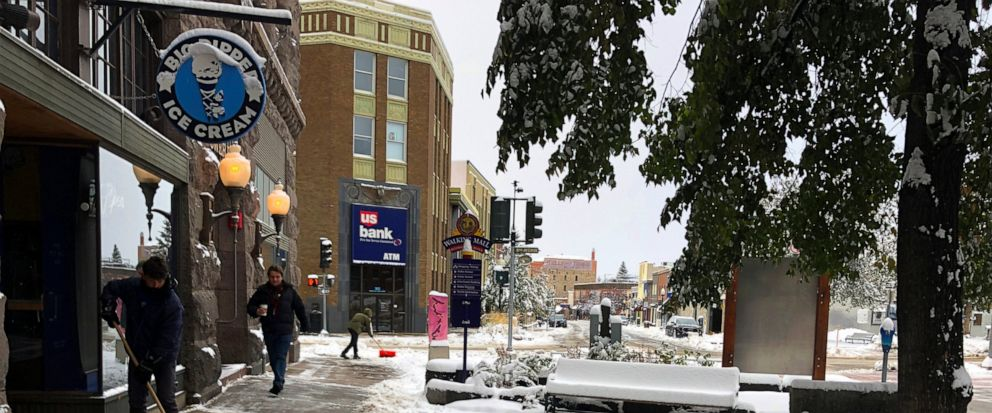 People clear the sidewalk after a fall snowstorm in Helena, Mont., on Wednesday, Oct. 9, 2019. The central Rocky Mountain region recieved its first dose of wintry weather. Mountainous areas recently hit by snowfall measured in feet (meters) could get