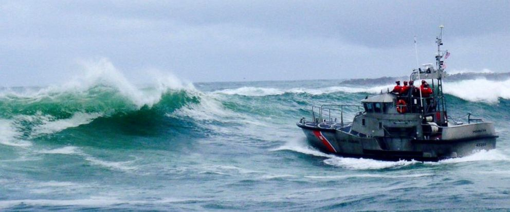 FILE - In this Tuesday, Jan. 8, 2019 file photo, provided by the U.S. Coast Guard, a U.S. Coast Guard boat crew responds to three fishermen in the water after the commercial fishing vessel Mary B II capsized while crossing Yaquina Bay Bar off the coa