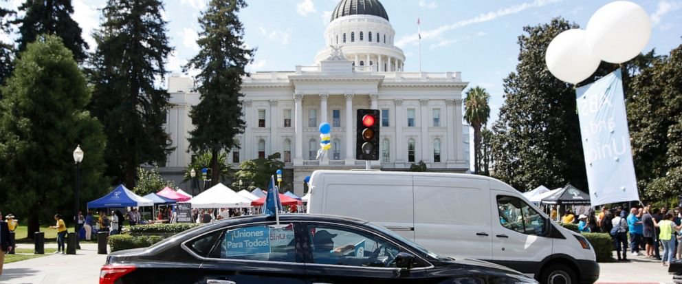 Dozens of supporters of a measure to limit when companies can label workers as independent contractors circle the Capitol during a rally in Sacramento, Calif., Wednesday, Aug. 28, 2019. If approved by the legislature and signed by Gov. Gavin Newsom,