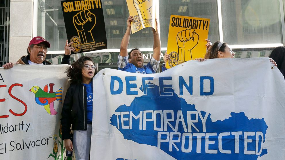 FILE - In this March 12, 2018 file photo, supporters of temporary protected status of immigrants cheer as they hold signs and banners with the outline of El Salvador at a rally at a federal courthouse in San Francisco. Immigrants from Honduras and Nepal have filed a lawsuit alleging the Trump administration unfairly ended a program that lets them live and work in the United States. The lawsuit filed late Sunday, Feb. 10, 2019, in federal court in San Francisco alleges that the U.S. Department of Homeland Security's decision to end so-called temporary protected status for the countries was motivated by racism. In 2018, a federal judge in San Francisco temporarily blocked the U.S. government from halting the program for immigrants from El Salvador, Haiti, Nicaragua and Sudan. The suit filed by citizens of those countries, much like this one, cited Trump's vulgar language during a meeting last year to describe African countries. (AP Photo/Jeff Chiu, File)