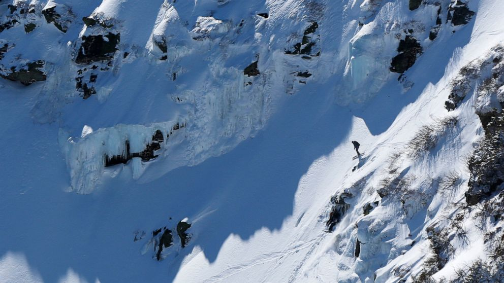 FILE - In this April 10, 2016, file photo, a skier drops below the ice-covered headwall of Tuckerman Ravine on New Hampshire's Mount Washington. On Friday, April 12, 2019, authorities warned that the possibility of further avalanches is increasing a day after a skier died when he was buried alive while skiing alone in a nearby area called Raymond Cataract on the Northeast's highest mountain. (AP Photo/Robert F. Bukaty, File)