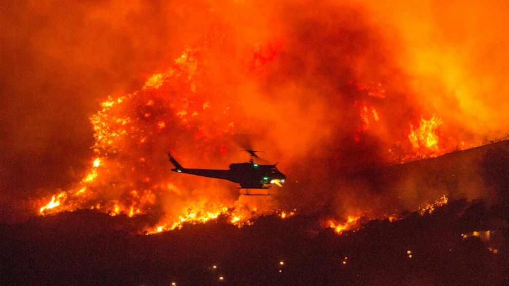 A helicopter prepares to drop water at a wildfire in Yucaipa, Calif., Saturday, Sept. 5, 2020. Three fast-spreading California wildfires sent people fleeing Saturday, with one trapping campers at a reservoir in the Sierra National Forest, as a brutal