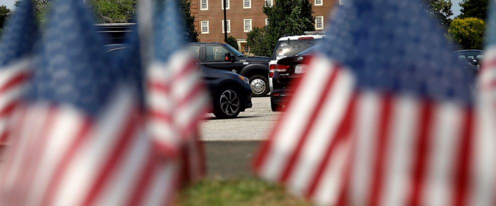 FILE - In this Saturday, June 1, 2019, file photo, American flags that are part of a makeshift memorial stand at the edge of a police cordon in front of a municipal building that was the scene of a shooting, in Virginia Beach, Va. A Virginia Beach ci