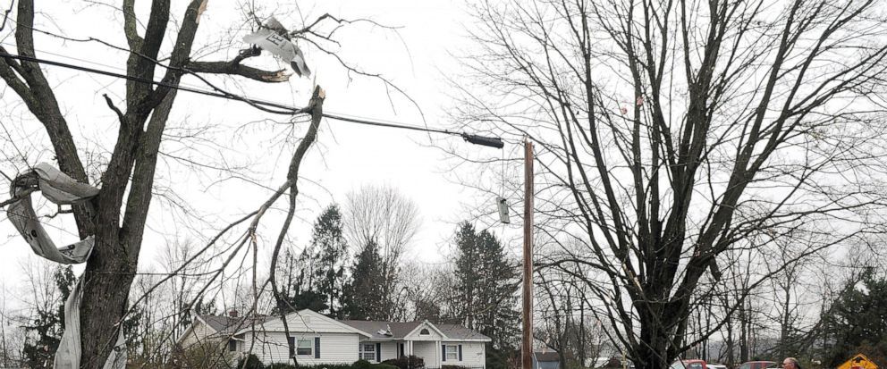 A Shelby firefighter walks down Plymouth Springmill Road just south of the intersection of Ohio Route 96, past damage to homes caused by severe weather, in Shelby, Ohio, Sunday, April 14, 2019. (Tom E. Puskar/The Times Gazette via AP)