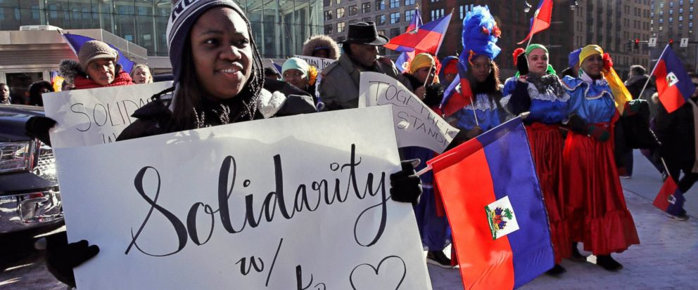 FILE - In this Jan. 26, 2018 file photo, Haitian activists and immigrants protest on City Hall Plaza in Boston. A trial in New York over the Trump administrations move to cut off permission for thousands of Haitians to live in the U.S. is spotlighti