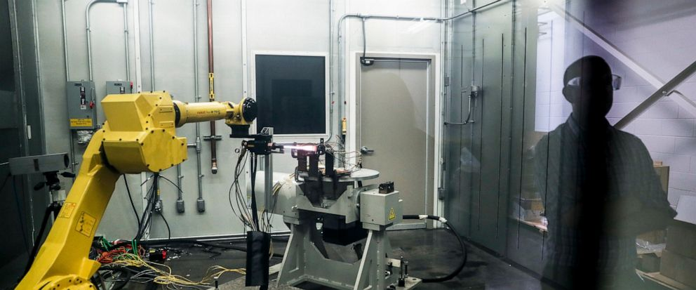 FILE - In this May 18, 2017, file photo, a robotic arm with a high-intensity blowtorch is remotely operated to test ceramic matrix composites, which make engines more durable, heat-resistant and efficient, at the General Electric Aviation plant in Ev