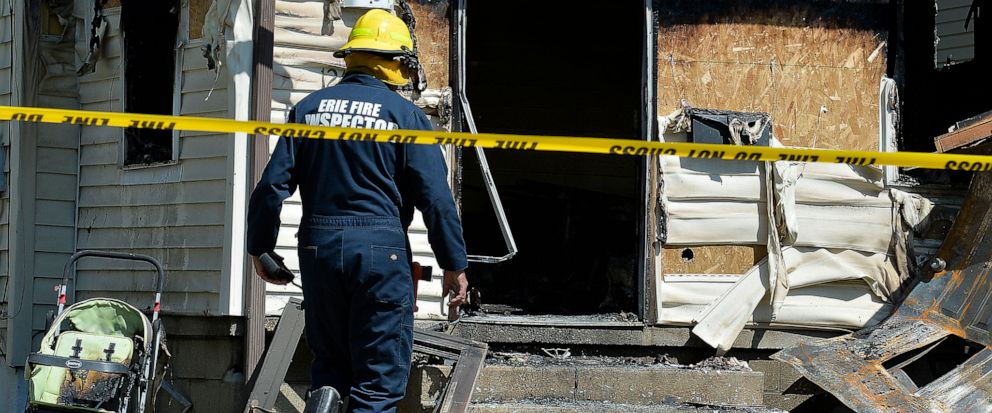 Erie Bureau of Fire Inspector Mark Polanski helps investigate a fatal fire at 1248 West 11th St. in Erie, Pa, on Sunday, Aug. 11, 2019. Authorities say an early morning fire in northwestern Pennsylvania claimed the lives of multiple children and sent