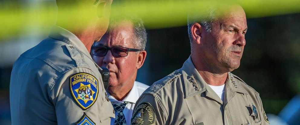 Riverside County Sheriff Chad Bianco, right, with Riverside City Police Chief Sergio G. Diaz, center, and a California Highway Patrol officer gather information after a shootout near a freeway killed a CHP officer and wounded two others before the gu