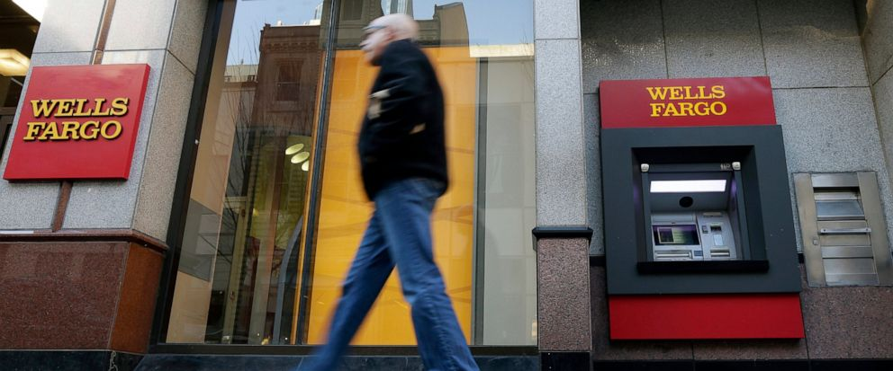FILE - In this Dec. 19, 2012, file photo, a man walks past a Wells Fargo branch in Philadelphia. Wells Fargo has agreed to pay at least $385 million to settle a California lawsuit alleging it signed up thousands of auto loan customers for costly car