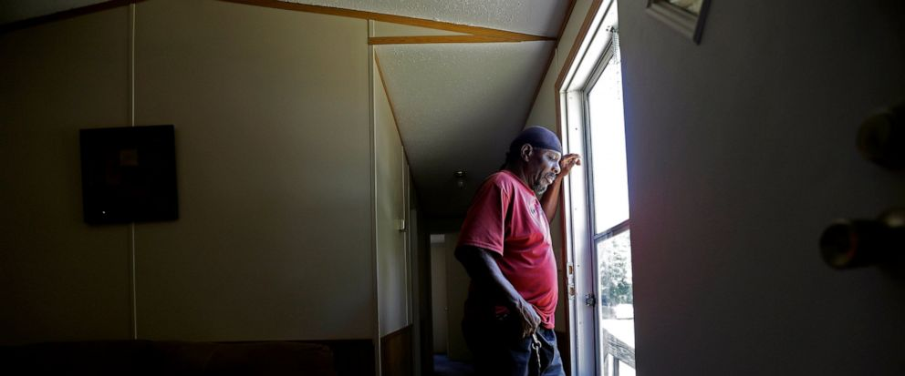 In this photo taken Wednesday, May 29, 2019, resident James Lesane stands at the entrance to his mobile home in Lumberton, N.C. Every month, Lesane pays what he can afford for his mobile home lot rental; $150. But, after the Florida-based company Tim