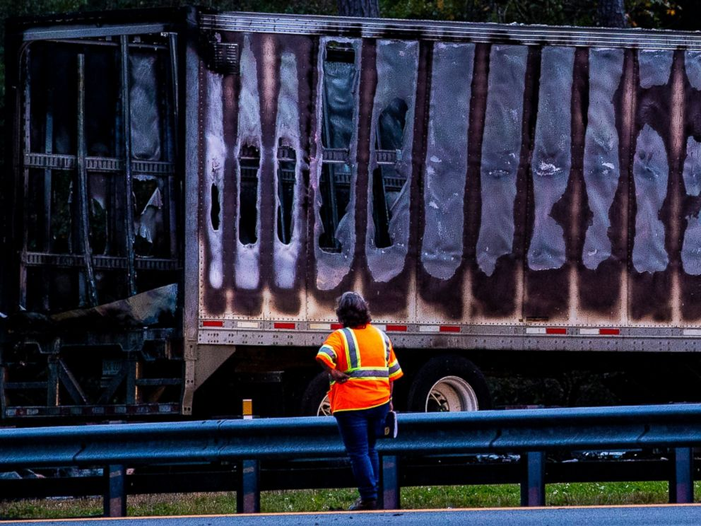 Workers look at a charred semi-truck after a wreck with multiple fatalities on Interstate 75, south of Alachua, near Gainesville, Fa., Thursday, Jan. 3, 2019. Two big rigs and two passenger vehicles collided and spilled diesel fuel across the Florida