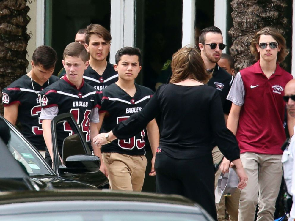 PHOTO: Members of the Marjory Stoneman Douglas High School football team depart the service at the Church by the Glades for Aaron Feis, the football coach who was killed at the school shooting last week, Feb. 22, 2018, in Coral Springs, Fla.