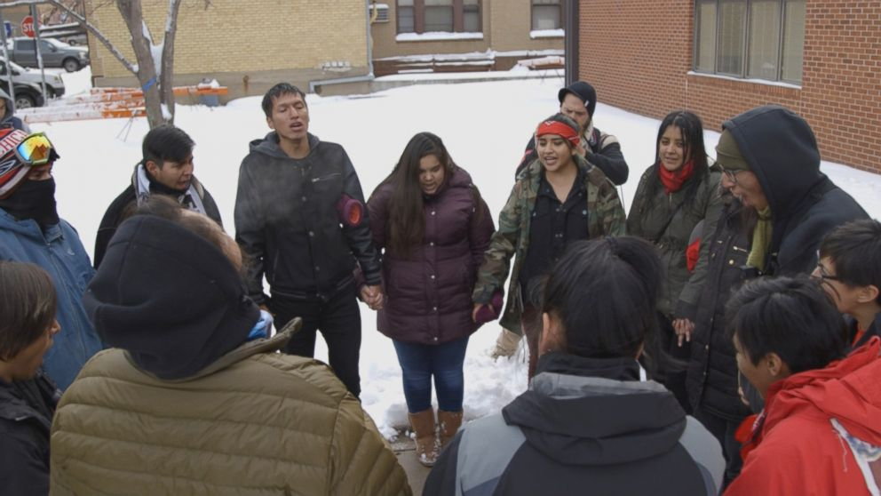 The International Indigenous Youth Council forms a prayer circle after delivering supplies to the Morton County Law Enforcement Center.