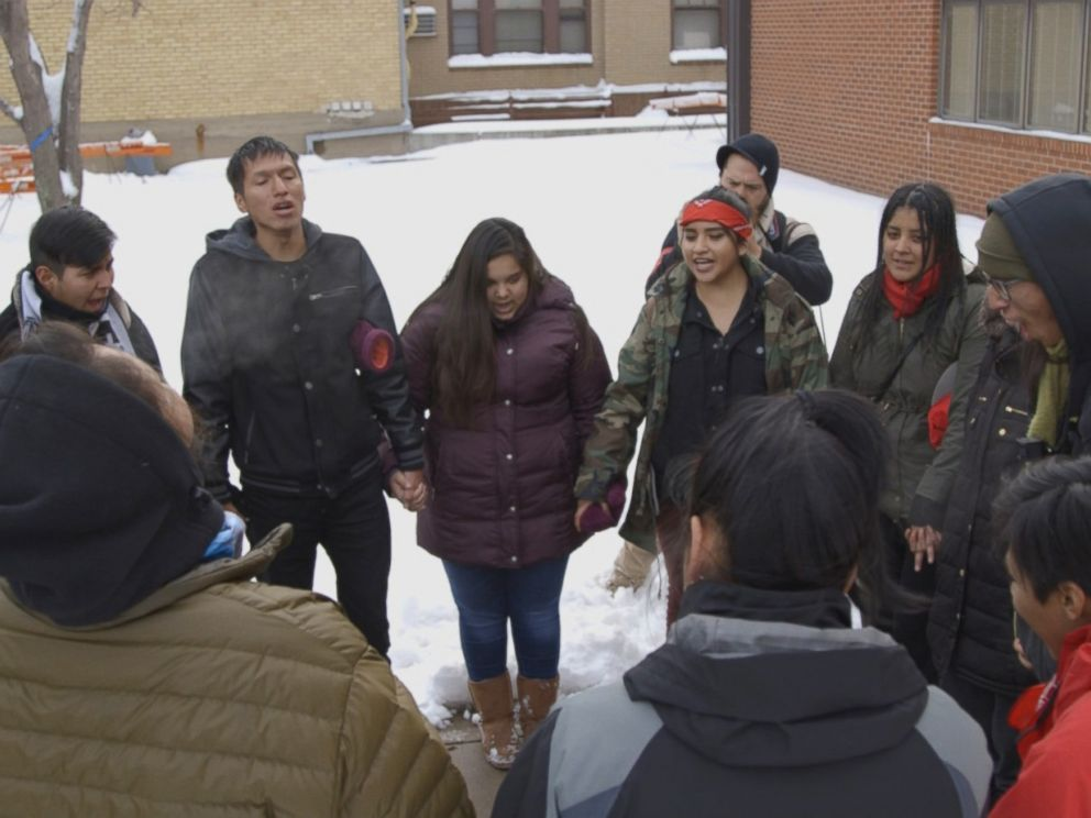 PHOTO: The International Indigenous Youth Council forms a prayer circle after delivering supplies to the Morton County Law Enforcement Center.