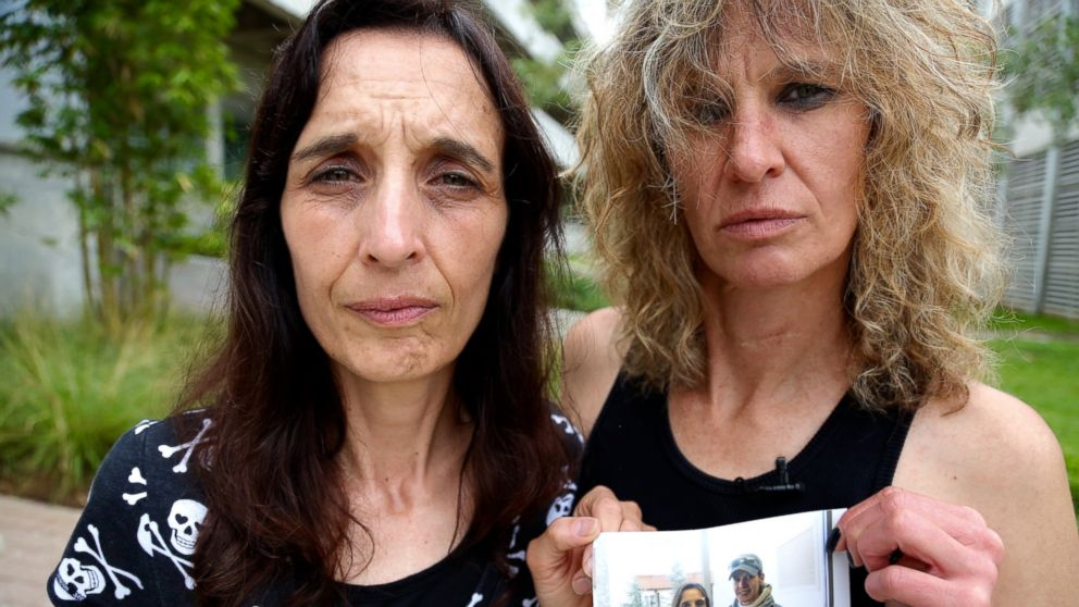 Leigh Erceg, right, and her friend Amber Anastasio, left, are shown here holding a picture of the two of them taken before Erceg's accident.
